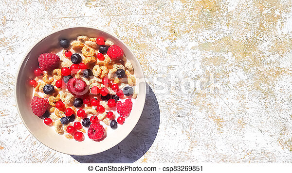 bowl of breakfast rings with milk and berries isolated on white background, top view.Delicious corn rings with berries on table.Healthy breakfast ,cereal rings in bowl with milk, honey, berries - csp83269851