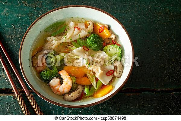 Bowl of Chinese wonton soup with dumplings - csp58874498