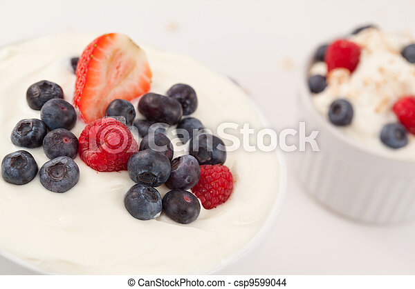 Bowl of cream with different berries  - csp9599044