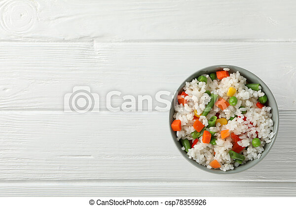 Bowl of delicious rice with vegetables on wooden background, top view - csp78355926