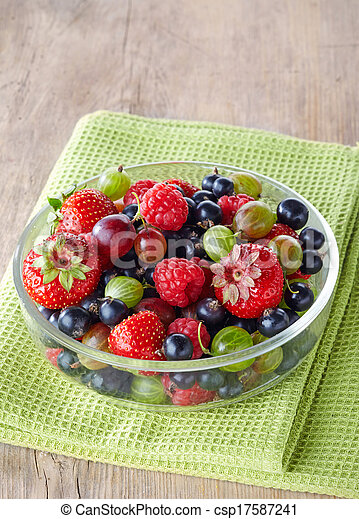 Bowl of fresh ripe berries on green tablecloth - csp17587241