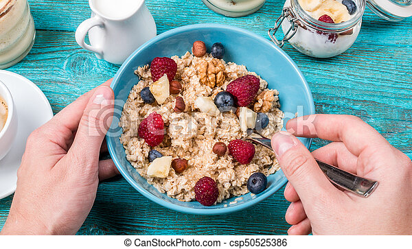 Bowl of oatmeal with raspberries and blueberries on a blue wooden table. - csp50525386