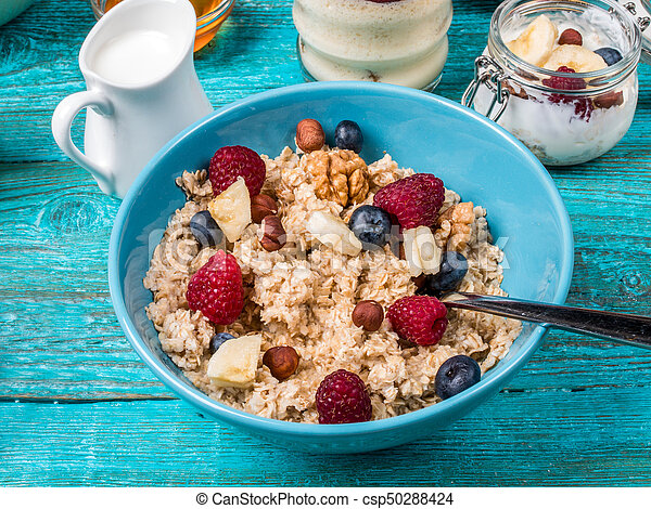 Bowl of oatmeal with raspberries and blueberries on a blue wooden table. - csp50288424