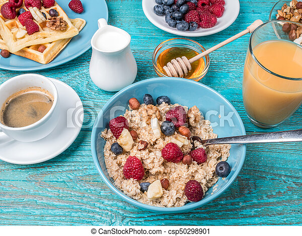Bowl of oatmeal with raspberries and blueberries on a blue wooden table. - csp50298901