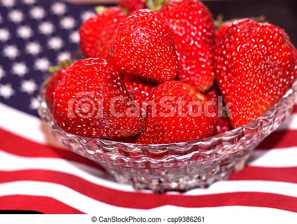 Bowl of ripe strawberries on 4th of July flag - csp9386261