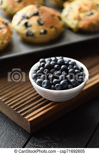 Bowl of ripe wild bilberries and freshly baked muffins on oak cutting board copy space. Low key still life with natural lighting - csp71692605