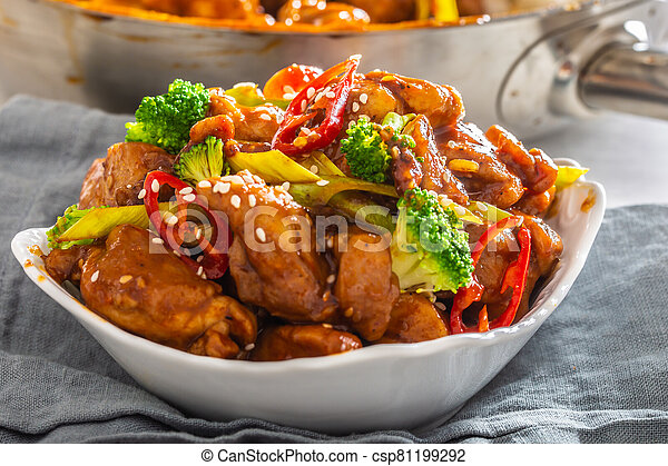 Bowl of teriyaki chicken sprinkled with seesame seeds, fresh chillies and broccoli - csp81199292