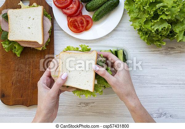 Mamá pone sándwiches en la lonchera. La mejor vista. Comida saludable. - csp57431800