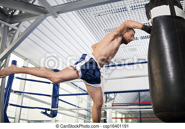 Boxer. Aggressive young kickboxer training at the punching bag - csp16401191