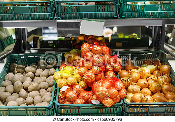 Boxes with ripe fresh potatoes and onions on shelves - csp66935796