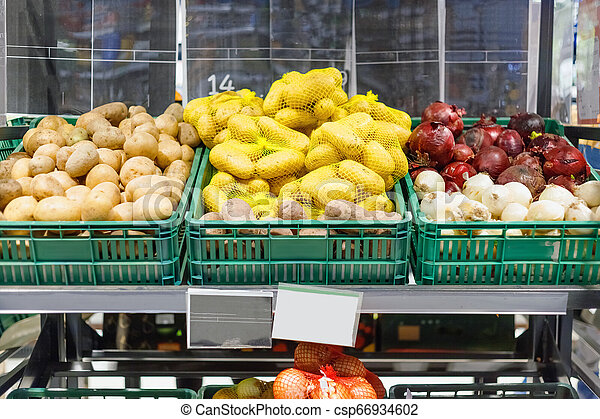 Boxes with ripe fresh potatoes and onions on shelves - csp66934602