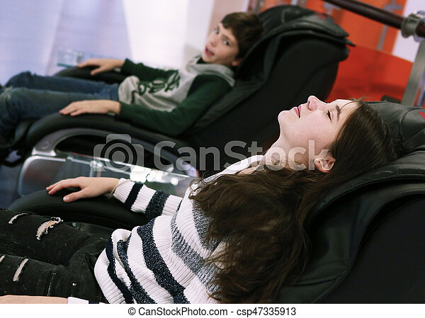 Boy And Girl In Massage Chair Close Up Photo