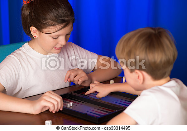 Boy and girl playing a board game called Backgammon - csp33314495