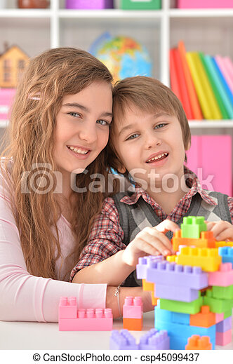 Boy and girl playing lego game - csp45099437