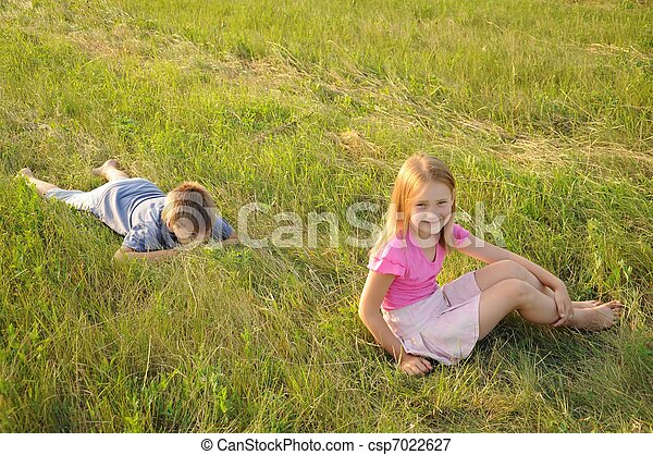 Boy and girl resting in a meadow - csp7022627