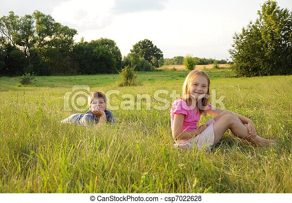 Boy and girl resting in a meadow - csp7022628
