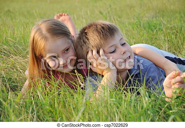 Boy and girl resting in a meadow - csp7022629