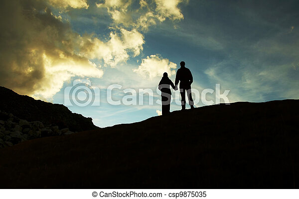 Boy and girl silhouette on sunset - csp9875035