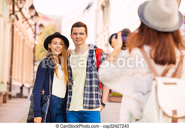 Boy and girl smiling with friend shooting them - csp32427243