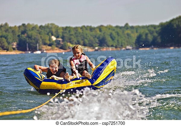 Boy and Girl Tubing Behind Boat - csp7251700