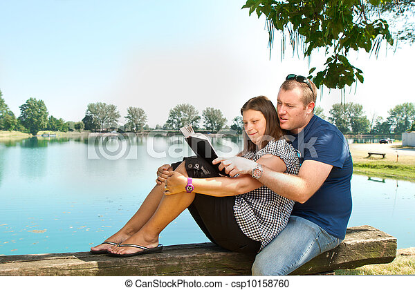 boy and girl with books on the nature near lake - csp10158760