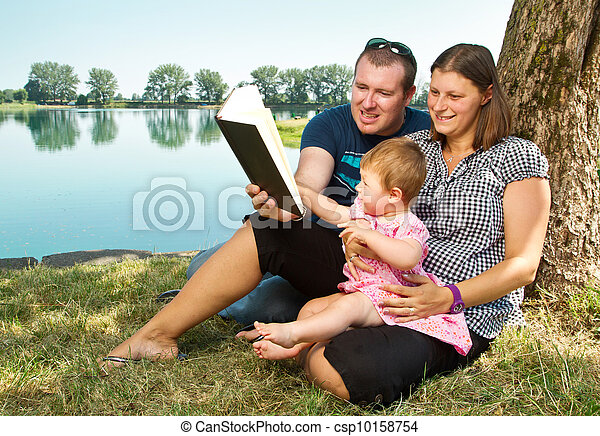 boy and girl with books on the nature near lake - csp10158754