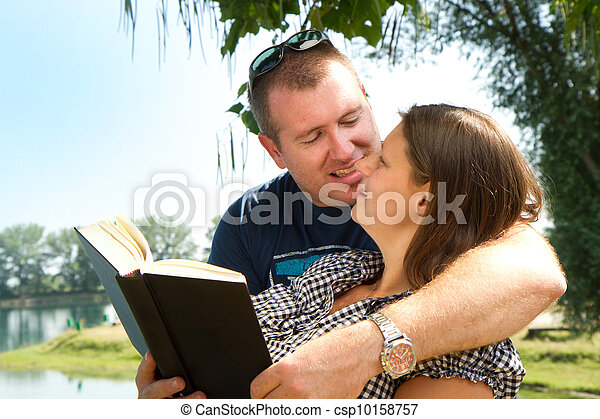 boy and girl with books on the nature near lake - csp10158757