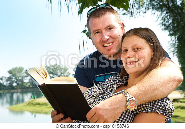 boy and girl with books on the nature near lake - csp10158746