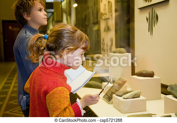 boy and little girl at excursion in historical museum near exhibits of ancient relics in glass cases - csp5721288