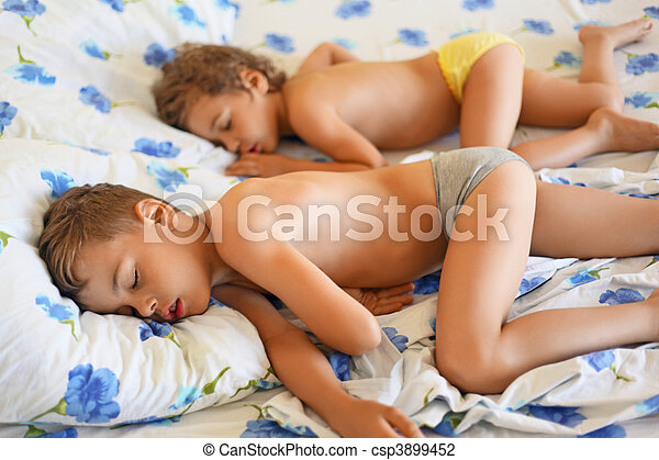 Boy And Pretty Little Girl Sleeping On Bed In Cosy Room
