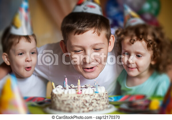 boy blows out the candles on a birthday cake and hugs his brother and sister - csp12170370