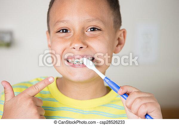 Boy brushing teeth and braces. - csp28526233
