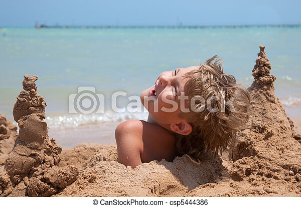 boy buried in sand - csp5444386