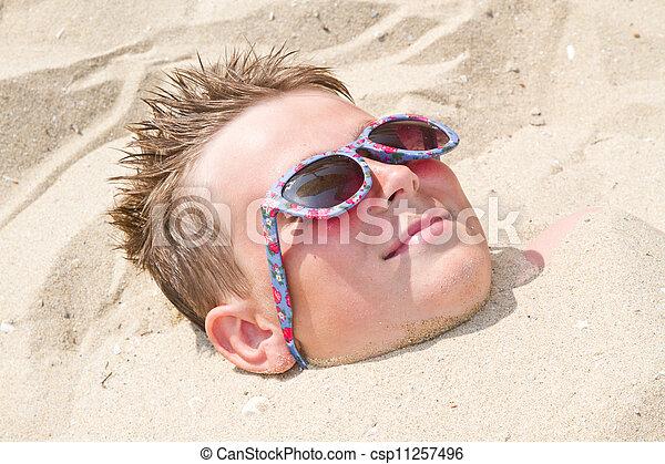 Boy buried in sand - csp11257496
