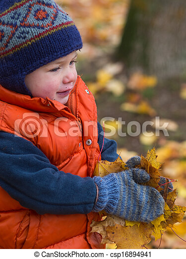 Boy carrying fall leaves - csp16894941
