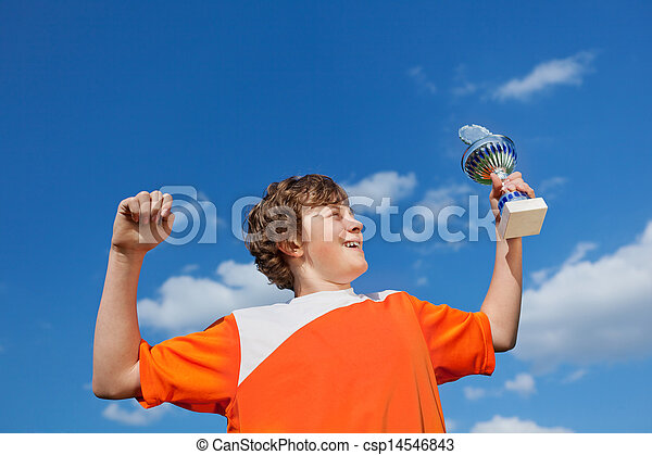 Boy Celebrating Victory While Holding Trophy Against Sky - csp14546843