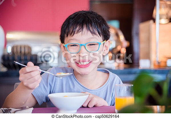 boy eating cereal for breakfast - csp50629164