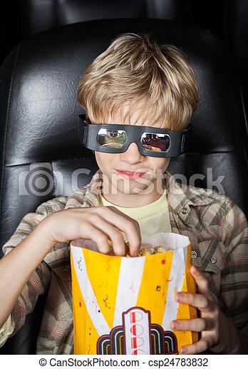 Boy Eating Popcorn While Watching 3D Movie - csp24783832