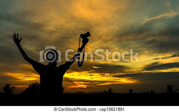 Boy hold camera silhoutte with orange skies - csp15621891