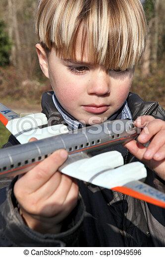 Boy holding a toy plane - csp10949596