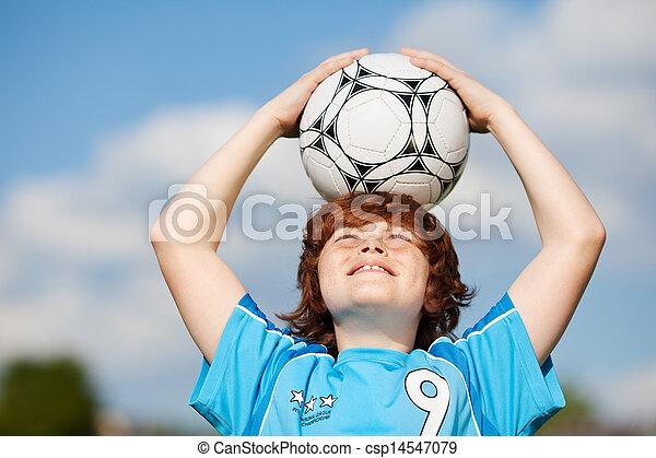 Boy Holding Soccer Ball On Head Against Sky - csp14547079