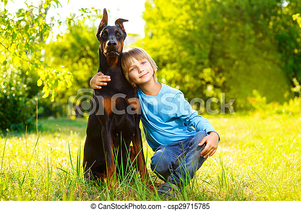 boy hugs his beloved dog or doberman in summer park - csp29715785