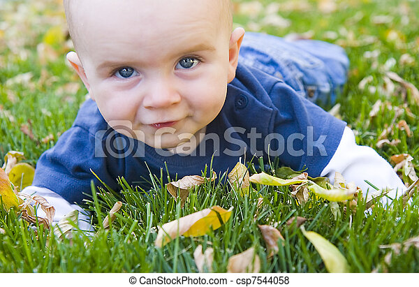 Boy in fall leaves - csp7544058