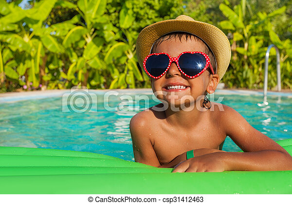 Boy in heart-shaped sunglasses on green airbed - csp31412463