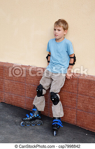 Boy in rollerblades, knee and elbow pads standing near wall. - csp7998842