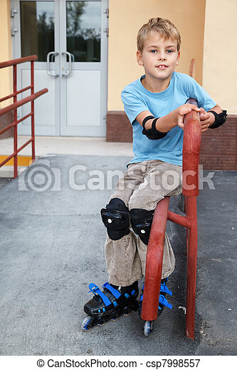 Boy in rollerblades, knee and elbow pads, sitting on the railing in front of house. - csp7998557