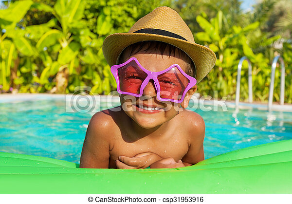 Boy in sunglasses on green airbed, swimming  pool - csp31953916