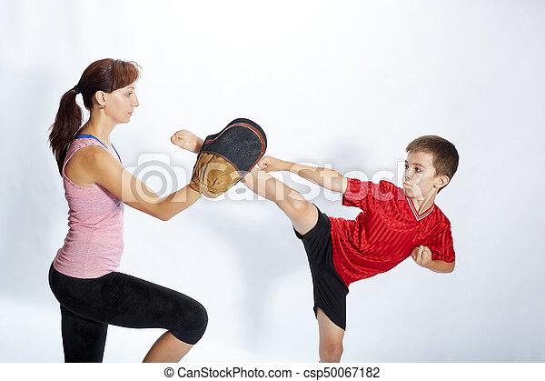 Boy is beating kick leg on the simulator that mom keeps - csp50067182
