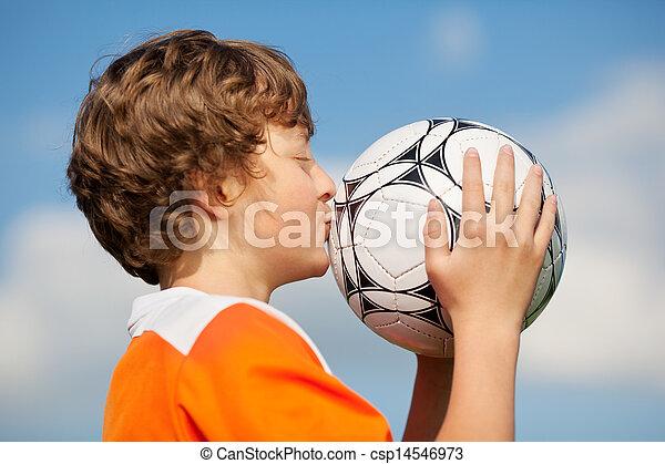 Boy Kissing Soccer Ball Against Sky - csp14546973