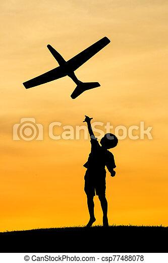 Boy launches toy plane. - csp77488078
